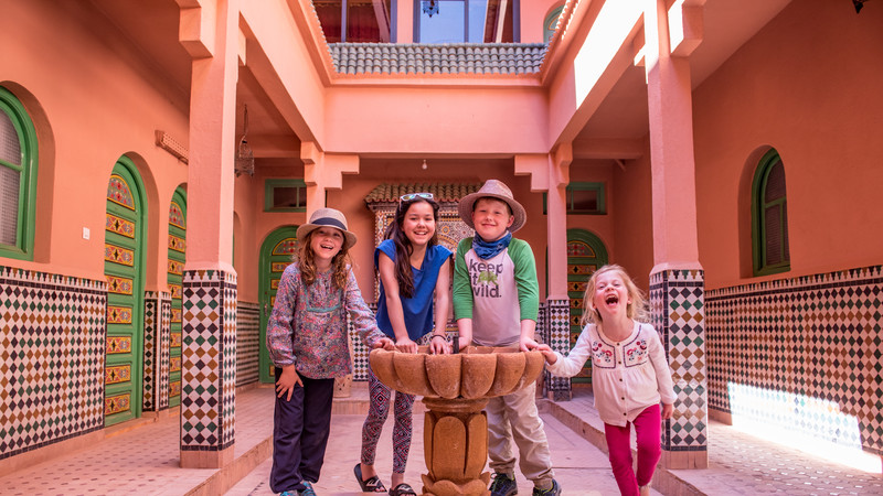 Kids stand around a fountain in a riad