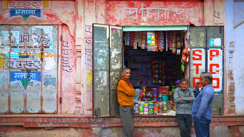 Three men standing outside a shop