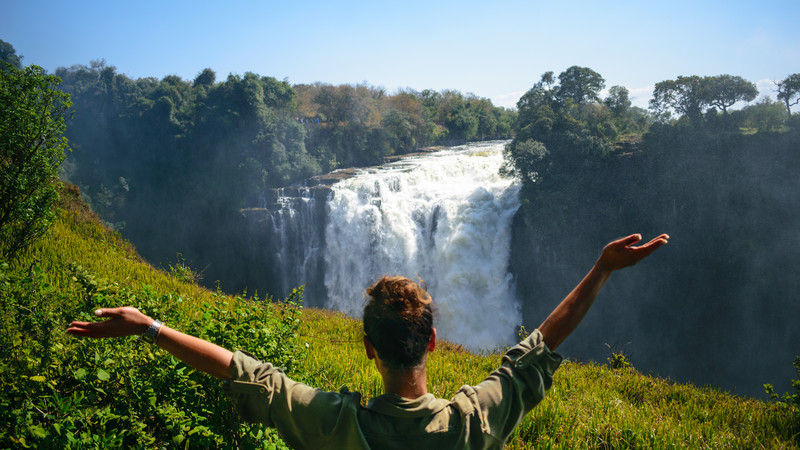 Girl with arms up looking at Victoria Falls