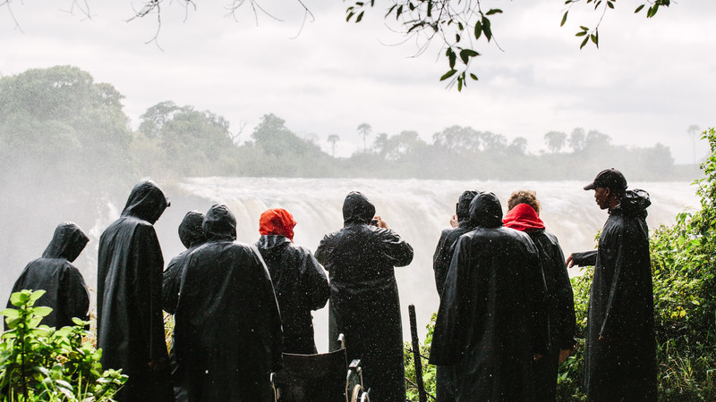 A group of travellers look at Victoria Falls
