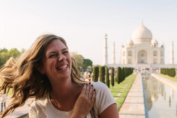 smiling female traveller in front of Taj Mahal