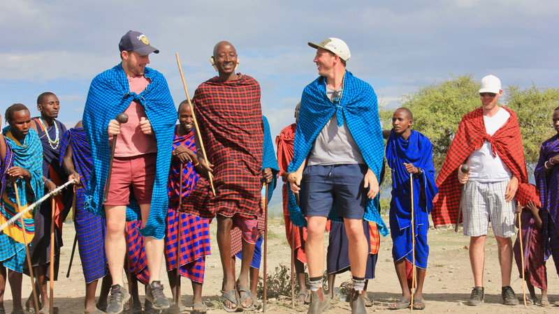 Two travellers jumping with Maasai warriors
