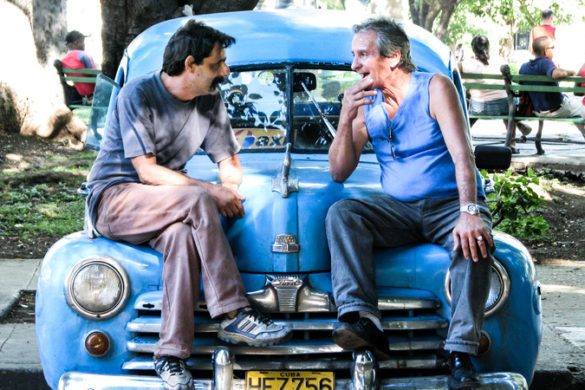 Two middle aged men sitting on the hood of a blue car, facing each other deep in conversation. In Havana, Cuba