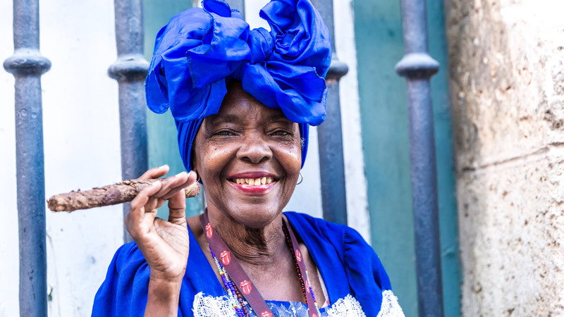 Portrait of African Cuban woman with blue headdress and clothing, happily smoking a cigar in Havana, Cuba.