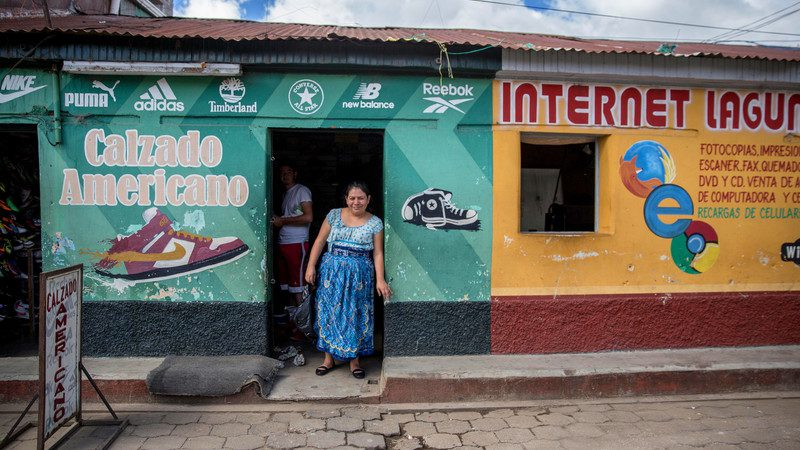 A woman stands outside her shop in Guatemala