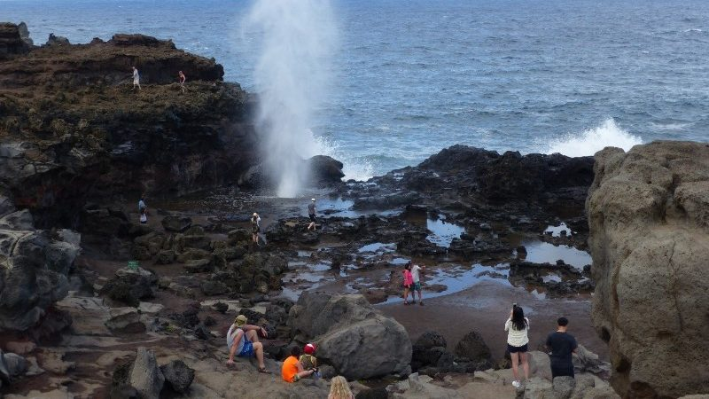 Travellers exploring a blowhole in Hawaii