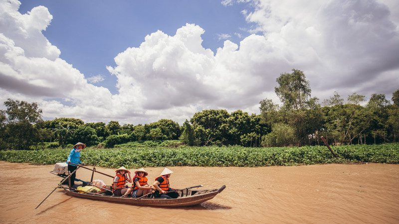 Three travellers in a boat on the Mekong Delta