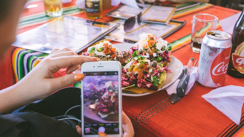 A traveller takes a photo of her food in Belize