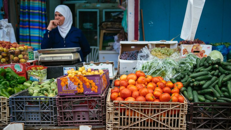 A shopkeeper sells fresh fruit at the market