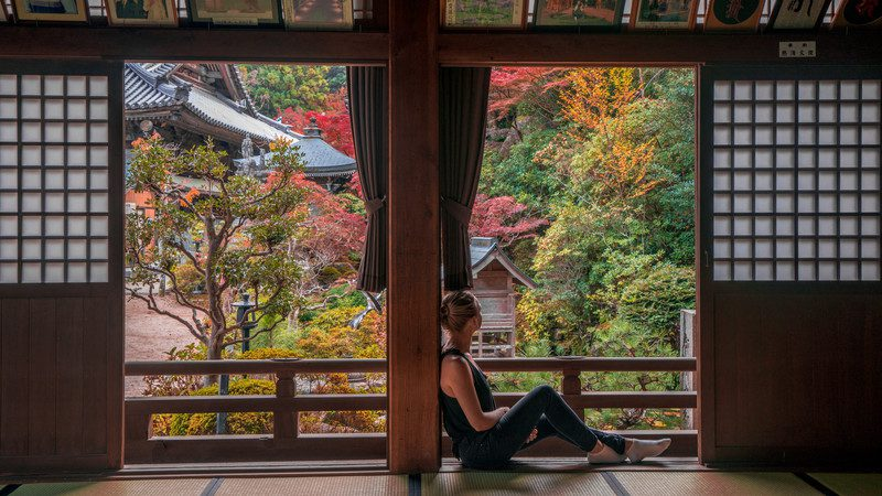 A girl looks out the window in a ryokan in Japan