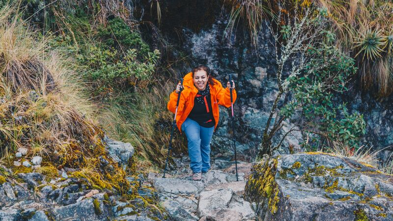 A female hiker in an orange jacket climbing up some stairs on the Inca Trail