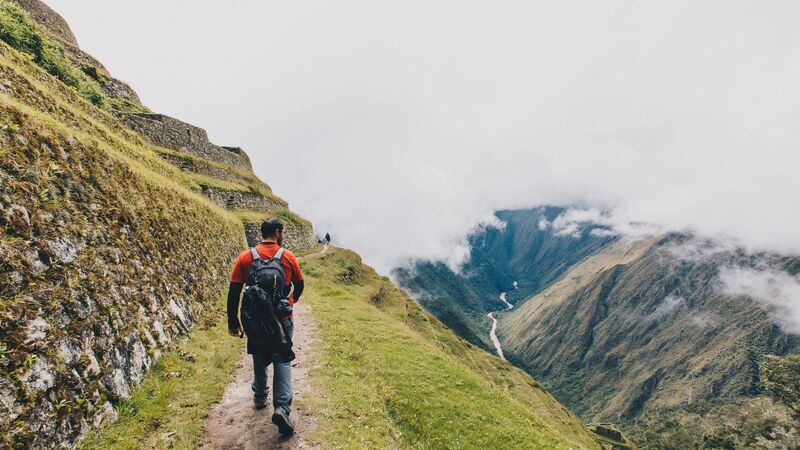 A male trekker wearing a backpack on the Inca Trail