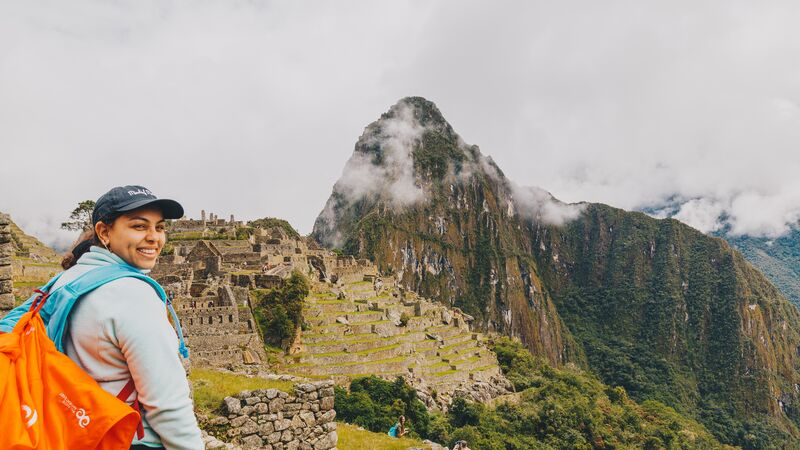 A young woman smiles at the camera at Machu Picchu