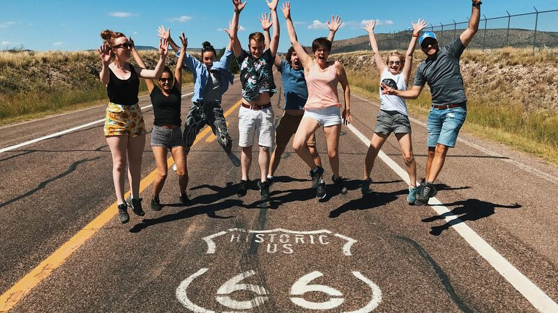 A group of travellers jumping in the middle of the road on Route 66.