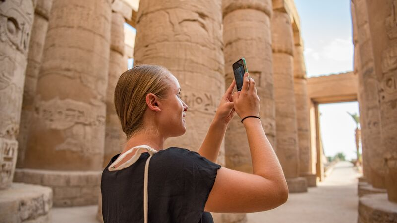 A young woman taking a photo in Egypt