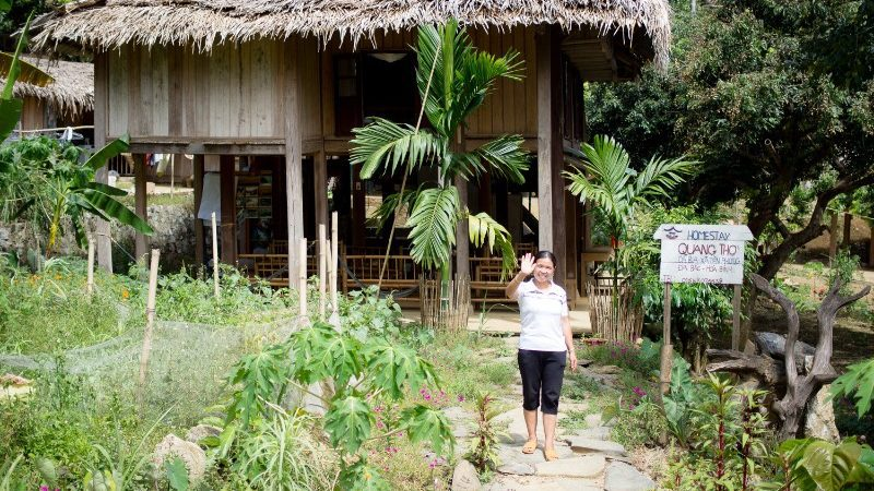 A woman waves outside her homestay in Da Bac