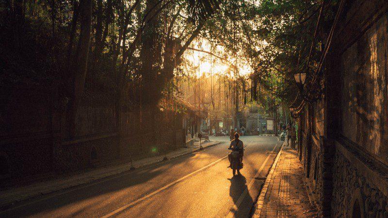Man motorbikes through Ubud at sunset