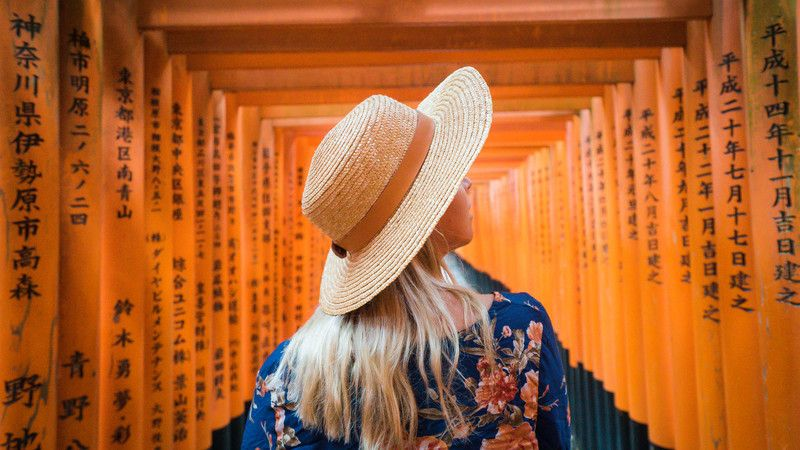 Girl walks through shrine in Japan.