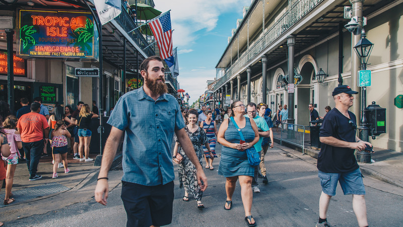 Travellers walk down Bourbon Street