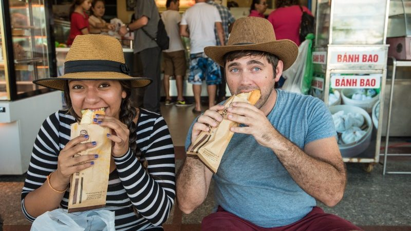 Two travellers eating banh mi sandwiches in Hoi An