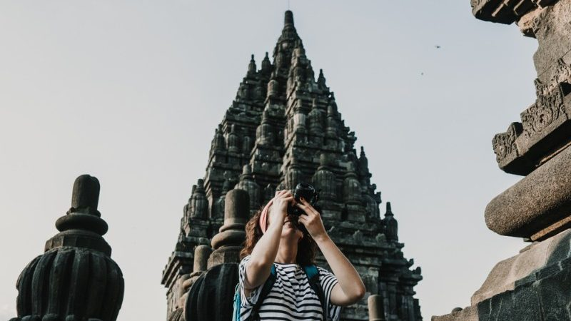 Woman taking photos of temple in Yogyakarta