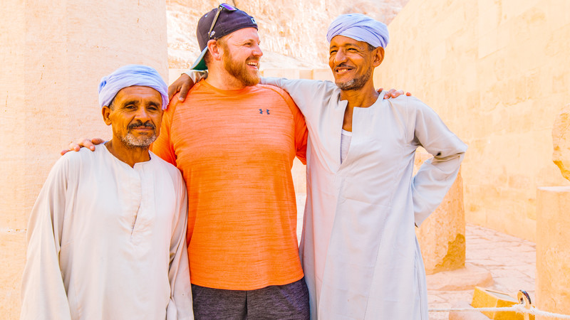 a traveller standing with two local men in Egypt