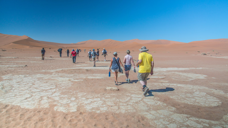 Travellers walking across the salt pans in Namibia