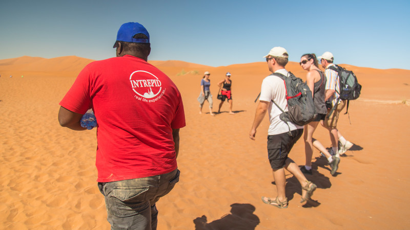 An Intrepid leader and travellers on a sand dune