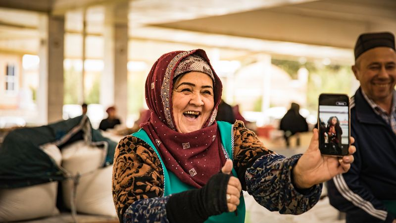 old Uzbek woman with phone laughing