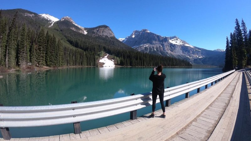 A woman takes a photo in the Rocky Mountains, Canada