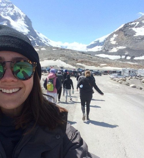 A woman takes a selfie in the rocky mountains