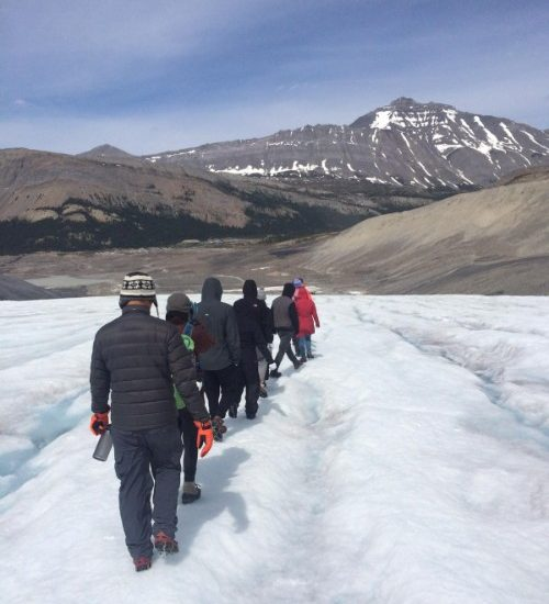 Travellers hike across a glacier in Canada