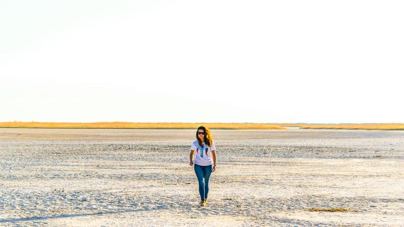 a woman walking on the Makgadikgadi salt pan.
