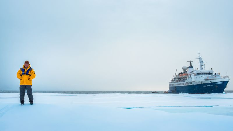 A traveller stands on the ice with a ship in the background