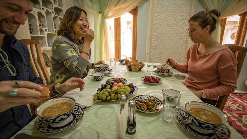 Travellers eating in traditional home in Bukhara