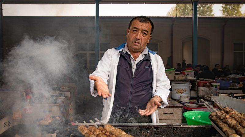 man selling kebabs at market