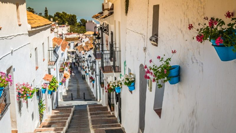 Colourful flowerpots hanging on white walled buildings in Mijas Pueblo, Spain