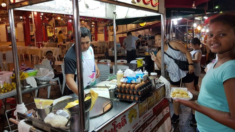 Girl in Thailand buying street food