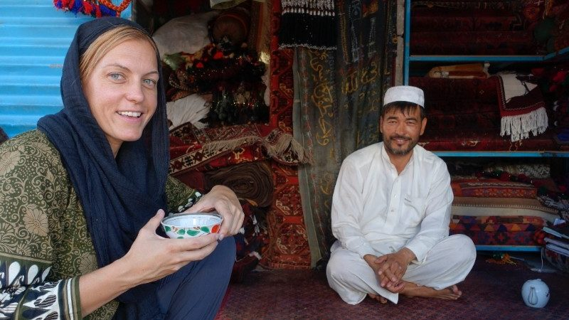 A young woman drinking tea with an Afghani man