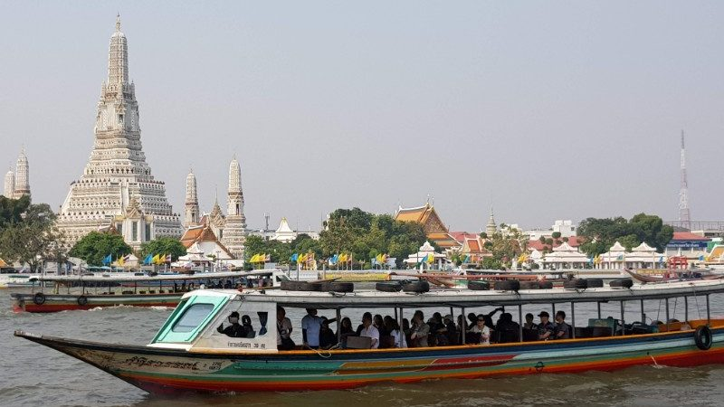 A long boat cruising past a temple in Bangkok
