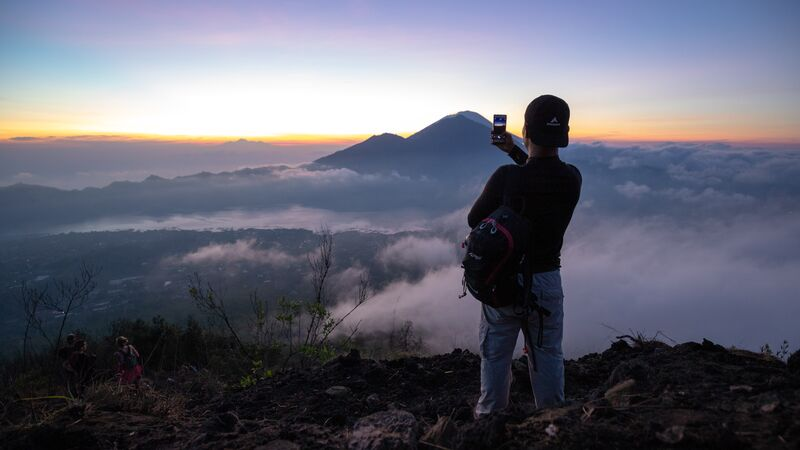 Traveller takes photo at Mt Batur, Bali.