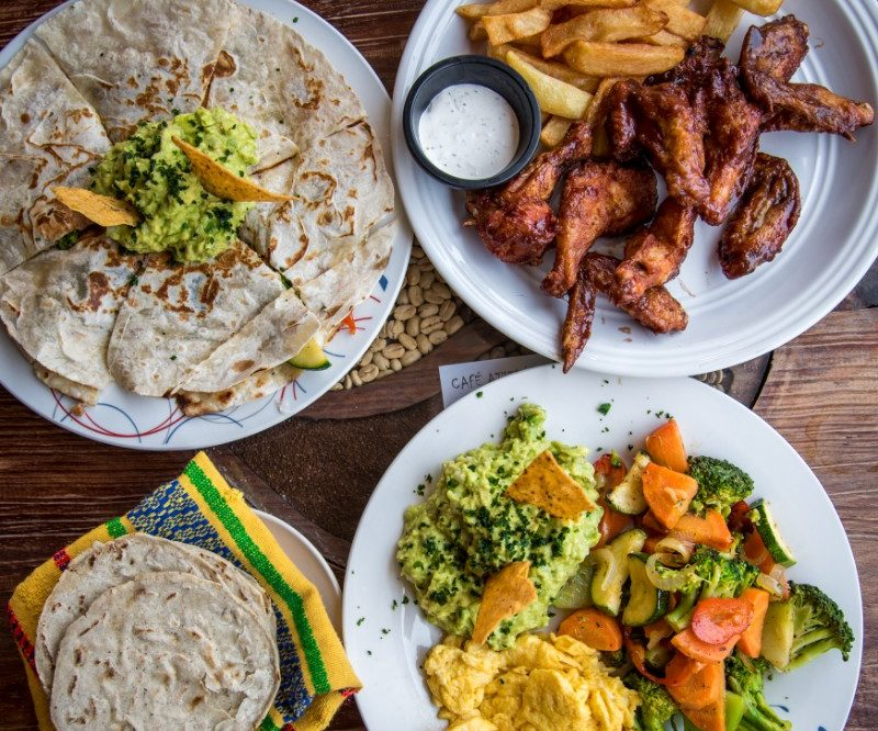 Plates of chicken, vegetables and bread
