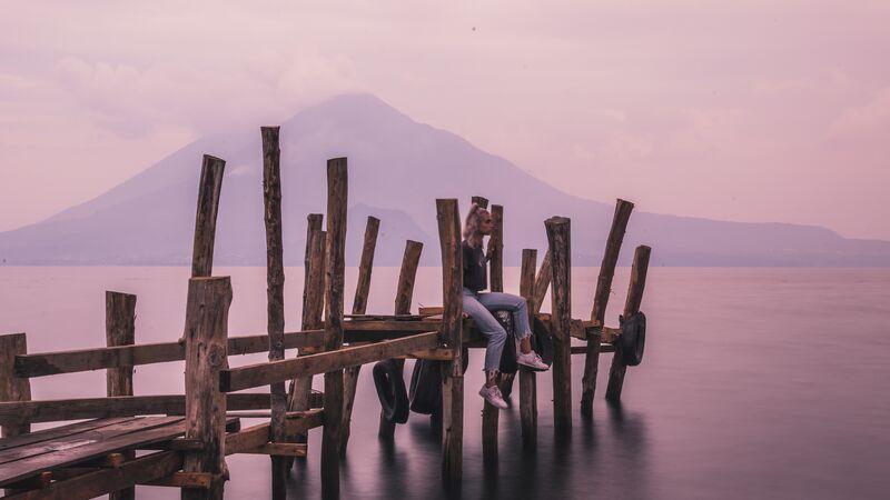 Girl sitting on the dock at Lake Atitlan, Guatemala