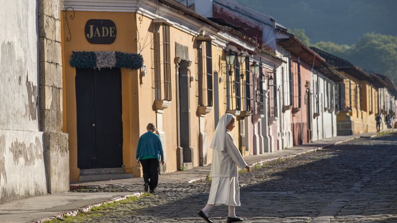 A nun walking along a cobbled street in Antigua