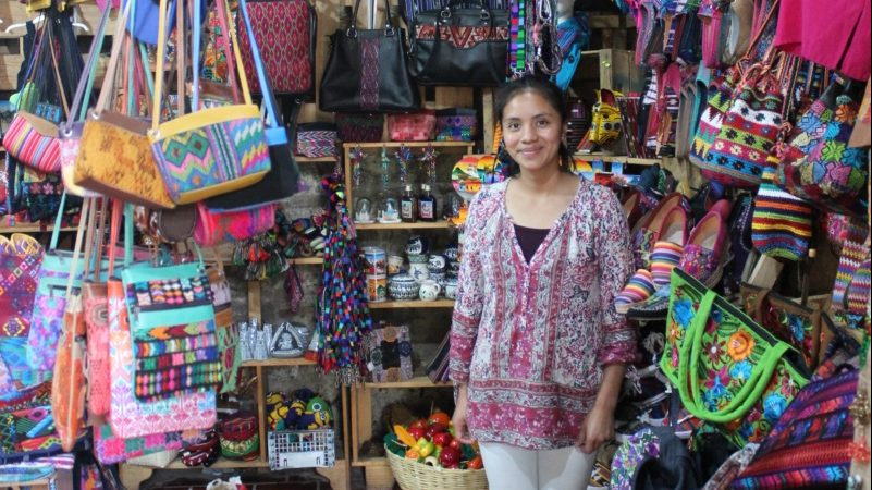 A woman stands in her shop full of handcrafted goods