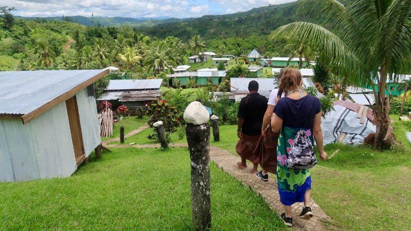 Travellers walk through a homesetay in Fiji