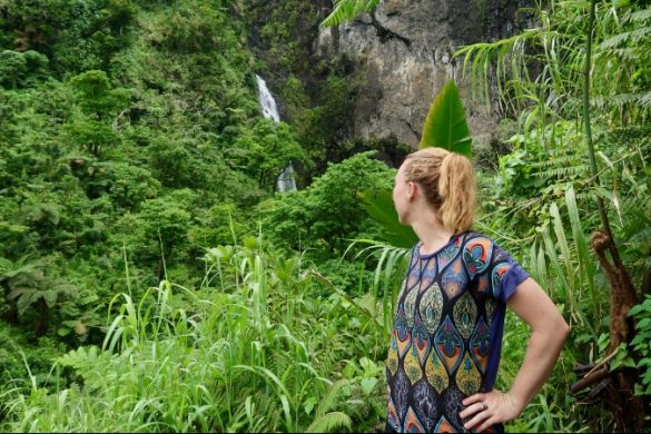 Woman looking at beautiful waterfall in Fiji