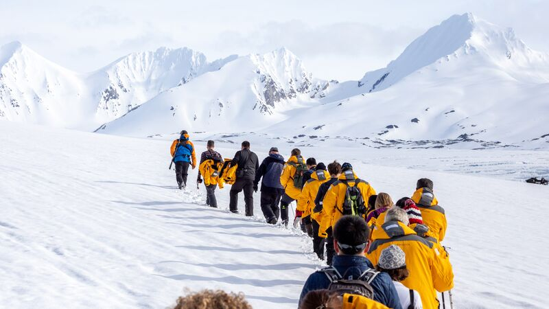 Travellers in yellow jackets walk across the ice