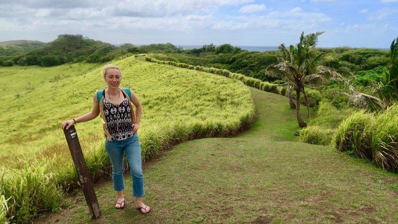 Woman hiking through green fields in Fiji