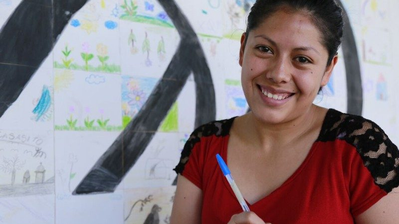 A young smiling woman with a pen and paper